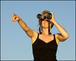 "alt=""Smiling woman with binoculars finds her destination in the distance"""