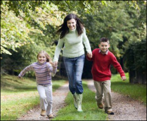 3217691-woman-outdoors-with-two-young-children-walking-on-path-holding-hands-and-smiling-selective-focus