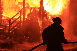 "alt=""Burning house in flames with silhouette of fireman"""