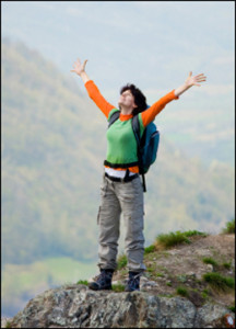 "alt=""Woman hiker on top of mountain with her arms raised showing her happiness at her achievement"""