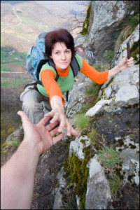 "alt=""Woman hiker on a mountain reaching for another hiker's helpful hand"""