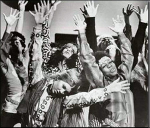 "alt=""Dancers from the 1960's with long hair, beads, raising their hands"""