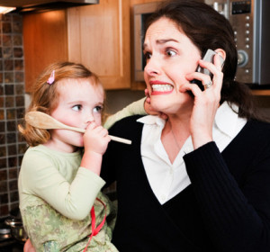 "alt=""Stressed working mom holding a small child, talking on phone"""